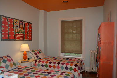 light blue bedroom with orange ceiling and colorful quilts