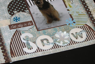 Closeup of the scrapbook page featuring BasicGrey Dasher and Figgy Pudding papers and uses stitching, layering and stamping; title is chipboard stamped with snowflake images and ribbon tied around it.
