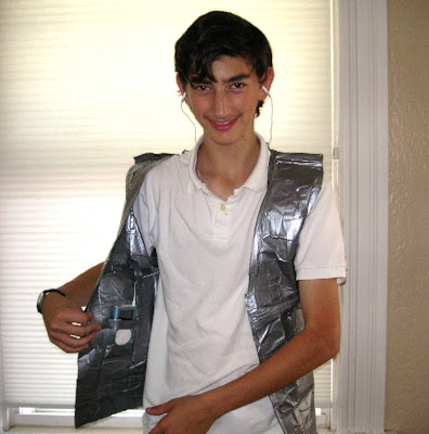 J, displaying the iPod pocket in his duct tape vest