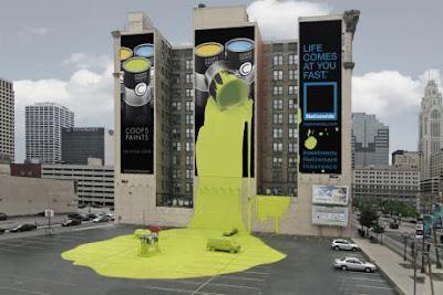 imagem de uma lata de tintas gigante derramada sobre um prédio e carros