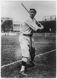 Babe Ruth, full-length portrait, standing, facing front, holding up bat, in baseball uniform, on field, Credit Line: Library of Congress, Prints & Photographs Division, [reproduction number, LC-USZ62-98072]