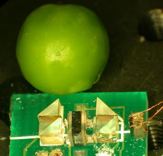 Caption: Photographed adjacent to an ordinary green pea, NIST's microfabricated spectrometer consists of a tiny container of atoms, a photodetector and miniature optics. Credit: Svenja Knappe/NIST, Usage Restrictions: None