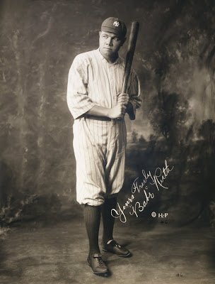 Babe Ruth in baseball uniform holding baseball bat
