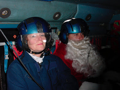Kodiak, AK (Dec. 5)--Santa Claus and his helper, Kathy Gundersen, relax aboard a Coast Guard helicopter on their way to Karluk. Santa and his staff traveled on Coast Guard helicopters to eight remote villages on Kodiak Island. USCG photo by PAC Marshalena Delaney