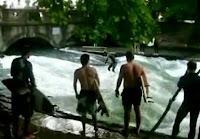 増水した川でサーフィンをする男性
