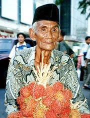 Javanese rambutan seller wearing Batik shirt and peci hat