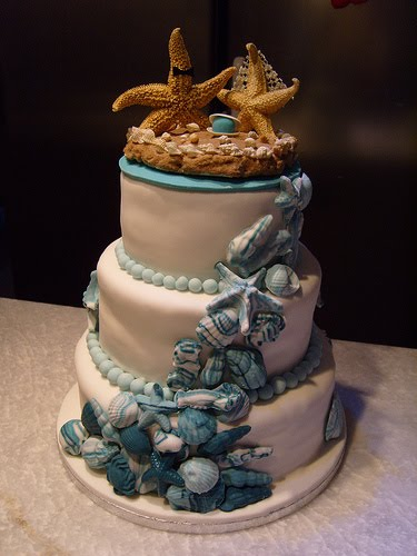 Elegant beach theme wedding cake encrusted with blue seashells and cute