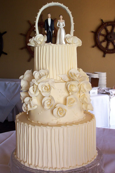 Elegant three tier round wedding cake with sugar roses emphasizing the