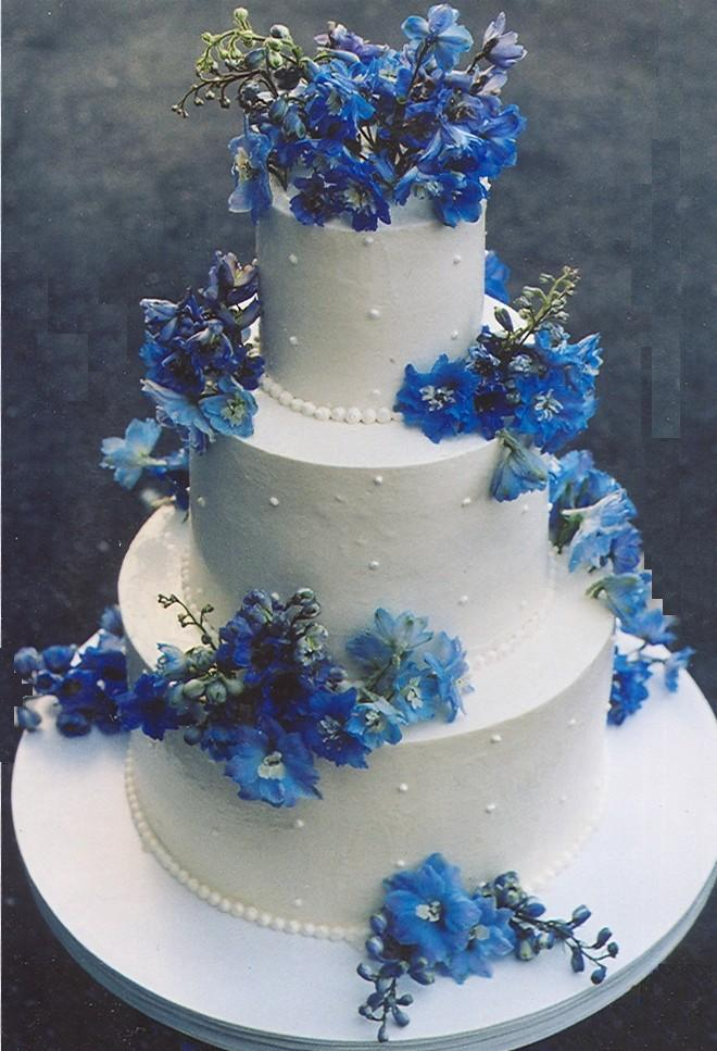 Three tier white wedding cake with edible pearl decorations and bright blue