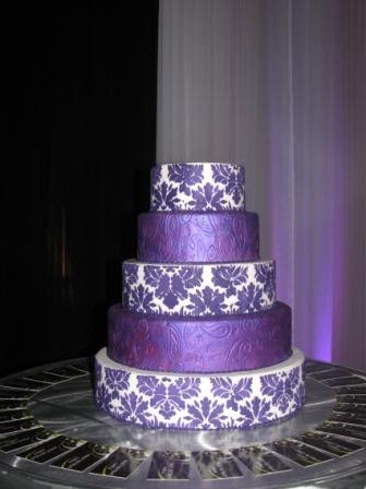 Purple Wedding Decorations on Three Tier Square White Wedding Cake With Purple Damask Pattern