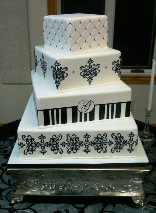 Lovely four tier black and white damask wedding cake with green satin ribbon