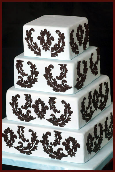 Elegant three tier square wedding cake with damask pattern and black satin