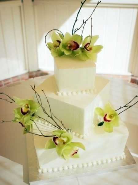 Four tier square white wedding cake with fresh green orchids