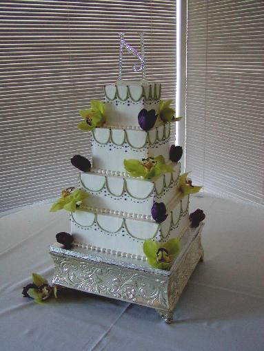 White wedding cake in white with four square tiers decorated with green