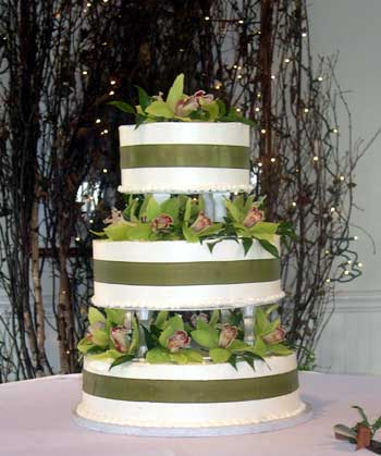 Whimsical green and white wedding cake set over four tiers white green