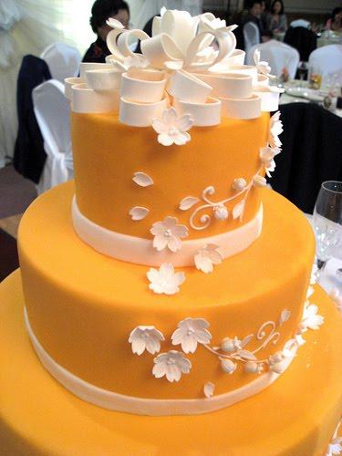 Bold orange wedding cake with white flowers