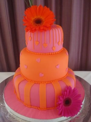 Orange and pink three tier wedding cake decorated with pink daisies original