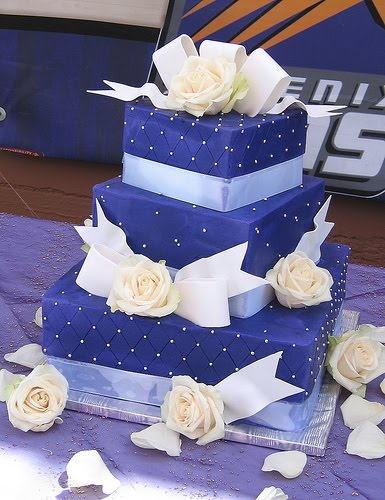 Deep rich purple square wedding cake decorated with white calla lilies