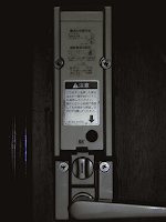 【照片:門內的門鎖。在注意事項下面的黑圈圈,就是要出去時,得按一下,從門外關上門後,才能扭動門鎖的電子鎖開關;而在電子鎖開關下面可以扭轉的就是門鎖;再下面的是開門的手把。】