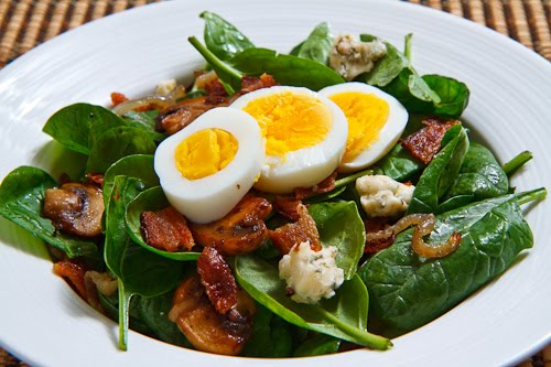 Spinach Salad with Bacon, Caramelized Onions, Mushrooms and Blue Cheese in a Bacon Pan Sauce Dressing Topped with a Hard Boiled Egg
