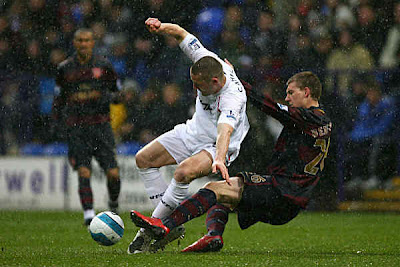 Gary Cahill of Bolton is tackled by Nicklas Bendtner of Arsenal.