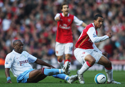 Theo Walcott of Arsenal is tackled by Nigel Reo-Coker of Aston Villa