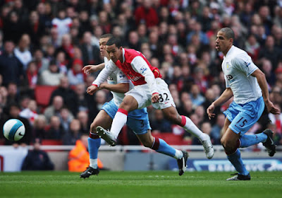 Theo Walcott of Arsenal gets a shot in while holding off the challenge of Wilfred Bouma and Curtis Davies of Aston Villa