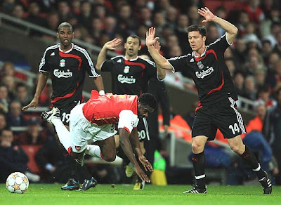 Xabi Alonso of Liverpool (R) stops Kolo Toure of Arsenal
