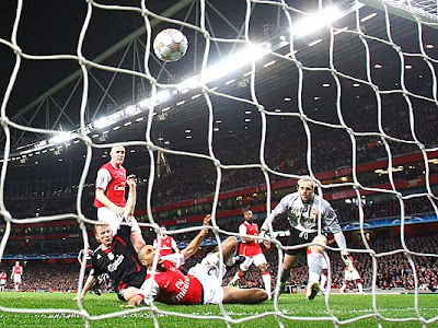Dirk Kuyt of Liverpool (L) beats Gael Clichy and Manuel Almunia of Arsenal to score the equalizing goal for Liverpool in the 26th minute