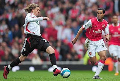 Theo Walcott of Arsenal closes down Leiva Lucas of Liverpool.