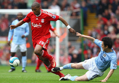 Ryan Babel of Liverpool is tackled by Jihai Sun of Manchester City