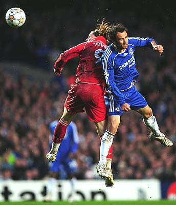 Fernando Torres of Liverpool jumps with Ricardo Carvalho of Chelsea.