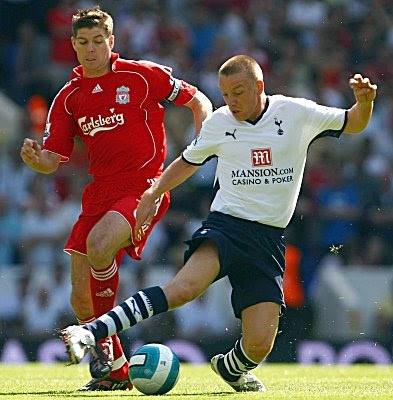 Jamie O'Hara of Tottenham Hotspur is challenged by Steven Gerrard of Liverpool during their Premier League match at White Hart Lane in London, England.