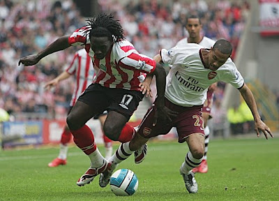 Kenwyne Jones of Sunderland and Gael Clichy of Arsenal challenge for the ball during their Premier League match at the Stadium of Light in Sunderland, England.