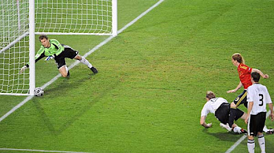 Germany goalkeeper Jens Lehmann (left) dives for the ball kicked by Spanish forward Fernando Torres (second right) in front of German defender Per Mertesacker (center) and defender Arne Friedrich (right).