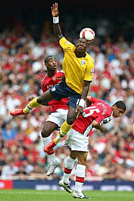 Ishmael Miller of West Bromwich Albion jumps for the ball against two Arsenal defenders.