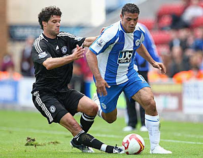 Amir Zaki of Wigan Athletic is tackled by Michael Ballack of Chelsea.