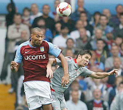 John Carew of Aston Villa leaps for the ball with Xabi Alonso of Liverpool.