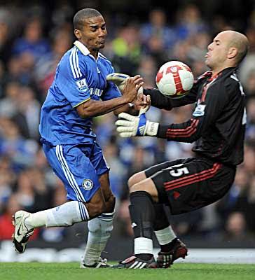 Florent Malouda of Chelsea runs into Liverpool goalkeeper Pepe Reina