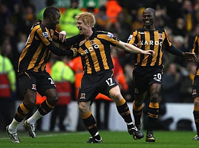 Paul McShane of Hull City celebrates scoring the opening goal with his team mate Kamil Zayatte (left) during the Barclays Premier League match between Liverpool and Hull City at Anfield in Liverpool, England