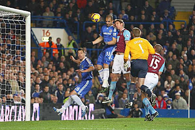 Calum Davenport of West Ham United makes a defensive clearance under pressure from Alex of Chelsea