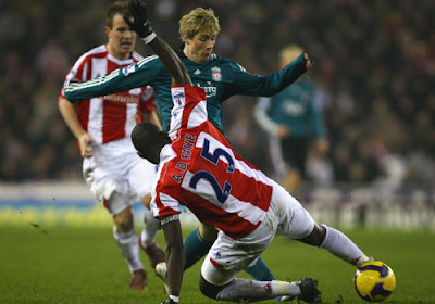 Fernando Torres of Liverpool is tackled by Abdoulaye Faye of Stoke City