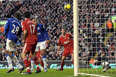 Everton defender Joleon Lescott (third left) scores the opening goal past Liverpool goalkeeper Jose Reina (right).