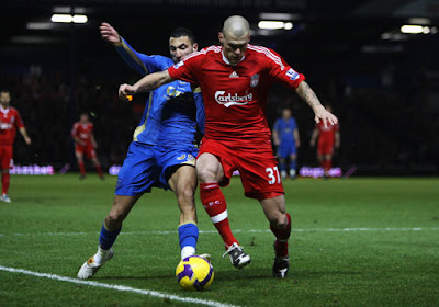 Martin Skrtel of Liverpool is confronted by Nadir Belhadj of Portsmouth