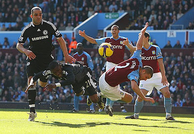 Salomon Kalou of Chelsea collides with Luke Young of Aston Villa.