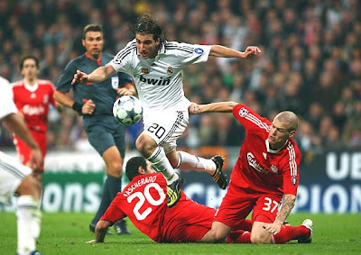 Martin Skrtel and Carlos Mascherano of Liverpool tackle Gonzalo Higuain of Real Madrid.