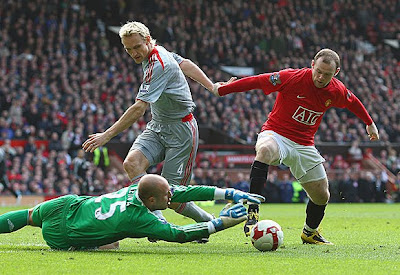 Pepe Reina of Liverpool dives to make a save at the feet of Wayne Rooney of Manchester United.