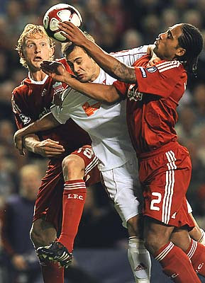 Liverpool's Dutch forward Dirk Kuyt (L) and English defender Glen Johnson (R) challenge Debrecen's Hungarian midfielder Peter Szakaly. The Reds won the match 1-0 thanks to Kuyt's goal at the end of the first half.