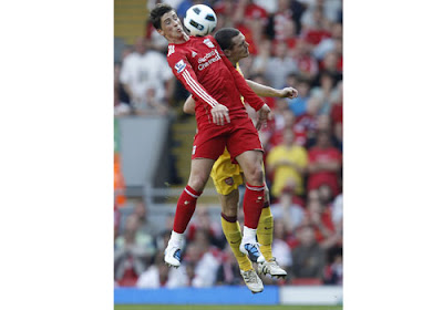Liverpool striker Fernando Torres jumps for the ball with Arsenal's Thomas Vermaelen