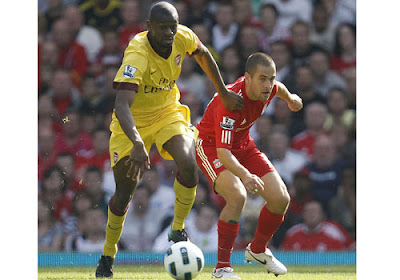 Abou Diaby of Arsenal tussles for the ball with Liverpool's Joe Cole